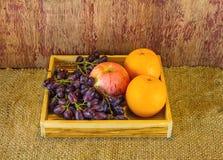Fruits (apple, orange , grape )  in an wood box, on sack sisal  Stock Images