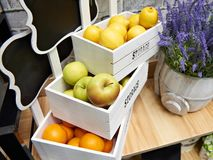 Fruits apples, oranges and lemons in white boxes in store. Fruits apples, oranges and lemons in white wooden boxes in the store Stock Photos