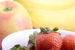 Fruits. Arrangement of various fresh ripe fruits: bananas, apple and strawberries closeup Royalty Free Stock Image