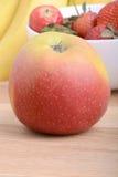 Fruits. Arrangement of various fresh ripe fruits: bananas, apple and strawberries closeup Stock Image