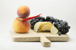 Fruits attacking junk food. Grapes, peaches, peppers attacking some chips Royalty Free Stock Photo