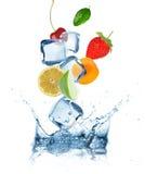 Fruits avec des glaçons éclaboussant dans l'eau images stock