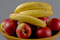 Fruits. Bananas and apples in wooden bowel Stock Photos