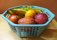 Fruits Basket. Green grapes, orange, pomegranate, bananas and apples inside a plastic fruits basket Stock Photography