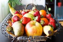 Fruits basket in living room. With strawberries, apples, pears, oranges, lemon, bananas stock photo