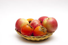 Fruits on a basket plate. Fruit composition: apples, pomegranate and persimmons on a basket plate Royalty Free Stock Images