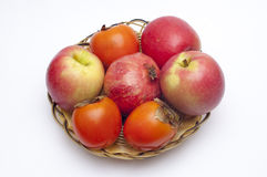 Fruits on a basket plate - top view. Top view of fruit composition: apples, pomegranate and persimmons on a basket plate Royalty Free Stock Images