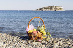 Fruits in a basket and wine in wineglasses. Different fruits in a wicker basket and wine in wineglasses against the background of the sea on a sunny day stock photography
