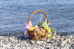 Fruits in a basket and wine in wineglasses. Different fruits in a wicker basket and wine in wineglasses against the background of the sea on a sunny day royalty free stock photos