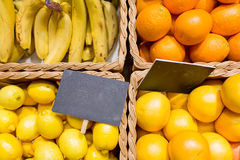 Fruits in baskets with nameplates at food market Royalty Free Stock Photos