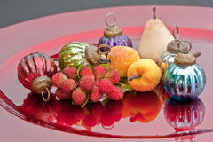 Fruits And Baubles. Sparkly fruit ornaments and glass baubles arranged on a red charger Royalty Free Stock Images