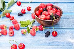 Fruits and berries in a bowl on a blue wooden background. Ripe raspberry, cherry, mulberry. Background blend of fruit stock photos