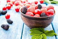 Fruits and berries in a bowl on a blue wooden background. Ripe raspberry, cherry, mulberry. Background blend of fruit stock photo
