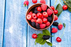 Fruits and berries in a bowl on a blue wooden background. Ripe raspberry, cherry, mulberry. Copy space. Background blend of fruit stock photo