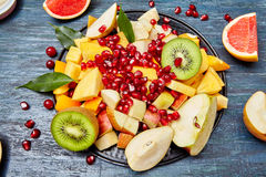 Fruits and berries for fruit salad. On blue rustic wooden background, top view. Copy space royalty free stock photos