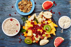 Fruits and berries for fruit salad. Oatmeal, nuts. Healthy breakfast concert, top view royalty free stock photos