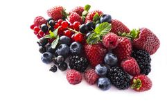 Fruits and berries isolated on white background. Ripe currants, raspberries, blueberries, strawberries and blackberries with a min. T leaf. Sweet and juicy Stock Image