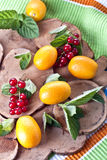 Fruits and berries. Kumquat and red currant over a wooden board Stock Photography