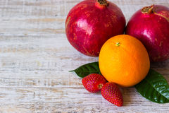 Fruits and berries on light background. Orange, strawberry and pomegranate on light background Stock Image