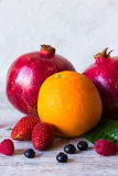 Fruits and berries on a light background. Pomegranates, orange, strawberries, raspberries and blueberries on a light background Royalty Free Stock Image