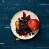 Fruits and berries lying on round plate. Standing on blue old wooden table - pear, plum, raspberry, blueberry, blackberry, red currant, pomegranate. Healthy Stock Image