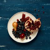 Fruits and berries lying on round plate. Standing on blue old wooden table - pear, plum, raspberry, blueberry, blackberry, red currant, pomegranate. Healthy Stock Photos