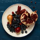 Fruits and berries lying on round plate. Standing on blue old wooden table - pear, plum, raspberry, blueberry, blackberry, red currant, pomegranate. Healthy Stock Images