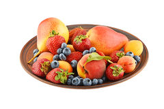Fruits and berries mix in ceramic plate isolated on white Royalty Free Stock Image