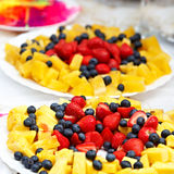 Fruits and berries on plate on the festive table. Royalty Free Stock Images
