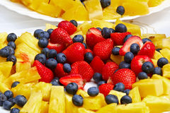 Fruits and berries on a plate on the table. Stock Photos