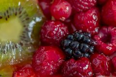 Fruits and berries in sweet gelatin on the cake. Background of strawberries, kiwi, currants, raspberry, blackberry. royalty free stock photo