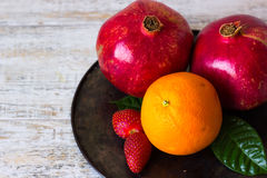 Fruits and berries on a tray. Strawberries, oranges and pomegranates on a tray Stock Images