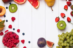 Fruits and berries on the white wooden background Royalty Free Stock Images
