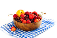 Fruits and berries in a wooden bowl on a checkered napkin. Gooseberries, strawberries, cherries, peaches are in a wooden bowl. on a blue checkered napkin. White Stock Images