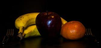 Fruits on black background. Bananas,orange and apple on black background with soft light Royalty Free Stock Photography