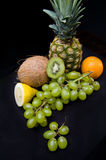 Fruits on black background  in studio. Grapes, oranges, pineapple, coconut Royalty Free Stock Photo