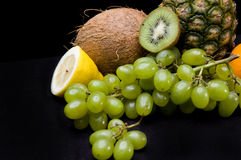 Fruits on black background  in studio. Grapes, oranges, pineapple, coconut Stock Photography