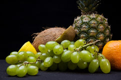 Fruits on black background  in studio. Grapes, oranges, pineapple, coconut Royalty Free Stock Image