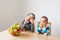 Fruits for breakfast. Children sitting at the table and eating apples Royalty Free Stock Image