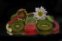 Fruits with candies. Multicolored fruits with candies on the mirror Stock Photo