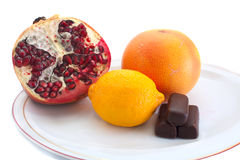 Fruits and candies on plate royalty free stock images