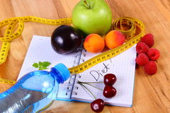Fruits and centimeter with notebook, slimming and healthy food. Fresh fruits, mineral water and tape measure with notebook for writing notes, concept of slimming Royalty Free Stock Photos
