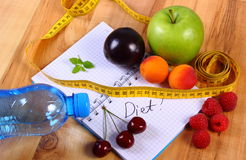 Fruits and centimeter with notebook, slimming and healthy food. Fresh fruits, mineral water and tape measure with notebook for writing notes, concept of slimming Stock Photos