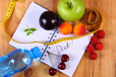 Fruits and centimeter with notebook, slimming and healthy food. Fresh fruits, mineral water and tape measure with notebook for writing notes, concept of slimming Stock Photography