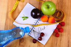 Fruits and centimeter with notebook, slimming and healthy food. Fresh fruits, mineral water and tape measure with notebook for writing notes, concept of slimming Royalty Free Stock Photography