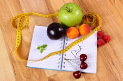 Fruits and centimeter with notebook, slimming and healthy food Royalty Free Stock Images