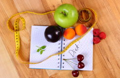 Fruits and centimeter with notebook, slimming and healthy food Stock Photos