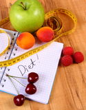 Fruits and centimeter with notebook, slimming and healthy food Royalty Free Stock Photography