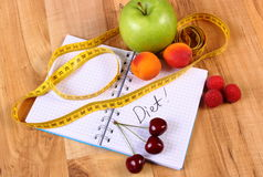 Fruits and centimeter with notebook, slimming and healthy food Stock Images
