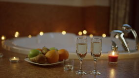 Fruits and champagne standing at the blurred background of water flowing in bath stock video